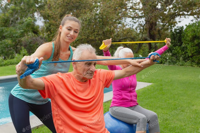 Caucasian female trainer assisting active senior Caucasian couple to exercise