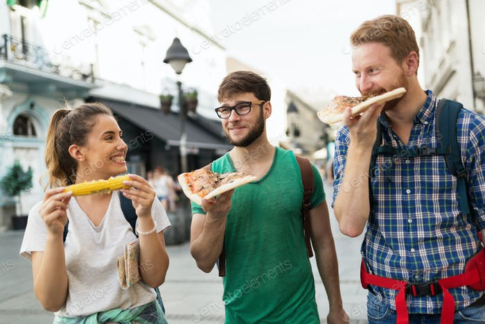 Happy people eating fast food in city