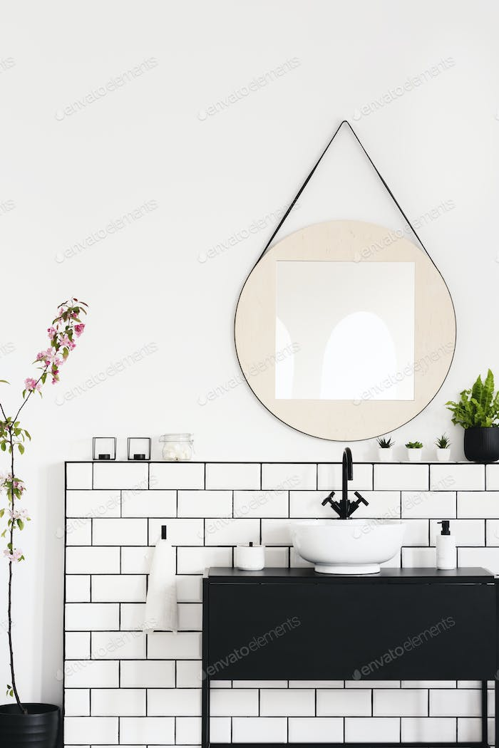 Real photo of a black cupboard, round mirror and white tiles in