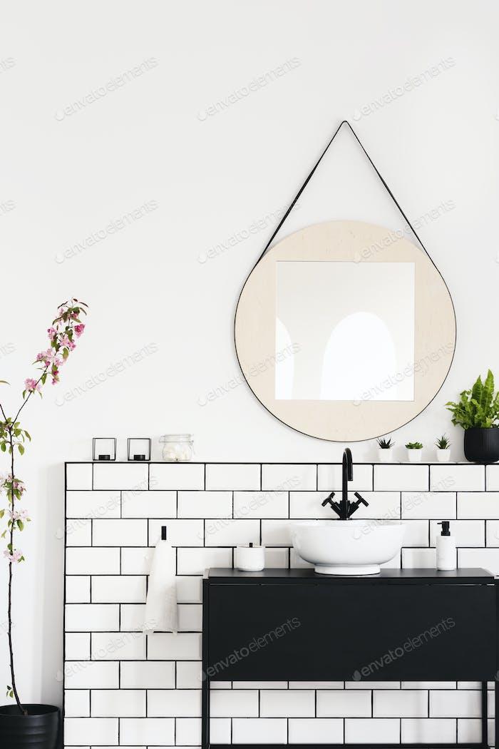 Echtes Foto von einem schwarzen Schrank, runden Spiegel und weißen Fliesen in