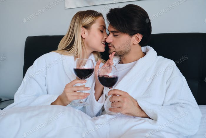 Young man and pretty blond woman in bathrobes dreamily kissing with glasses of red wine