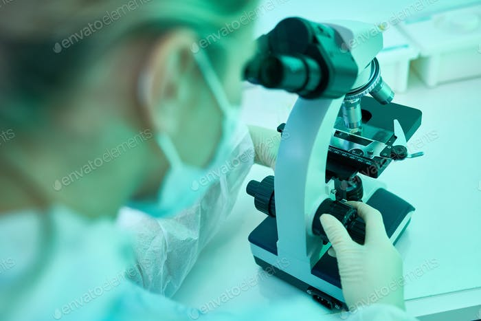 Woman Using Microscope in Lab
