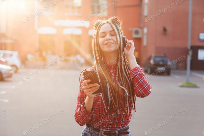 Молодая женщина с цветными косичками слушает музыку в наушниках в городе