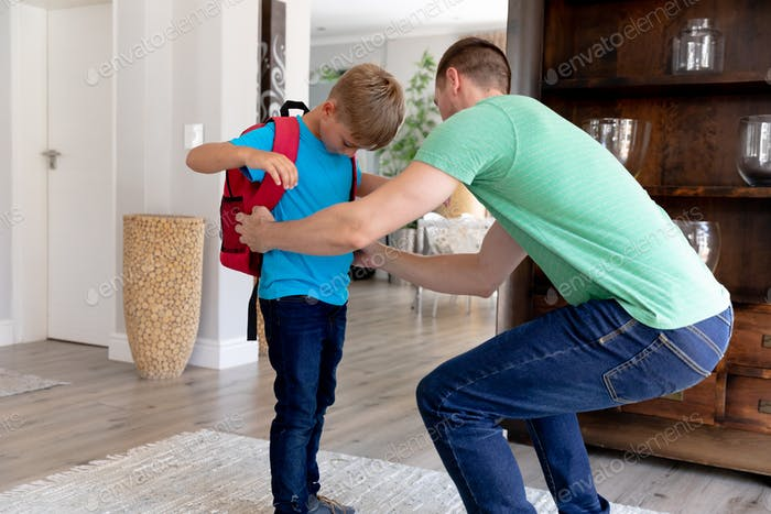 Caucasian man helping his son preparing for leaving to school.