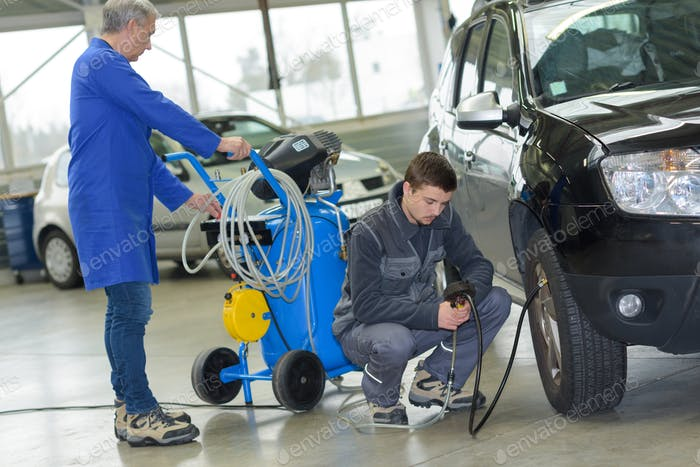 student and senior mechanic checking tyre pressure at automotive shcool