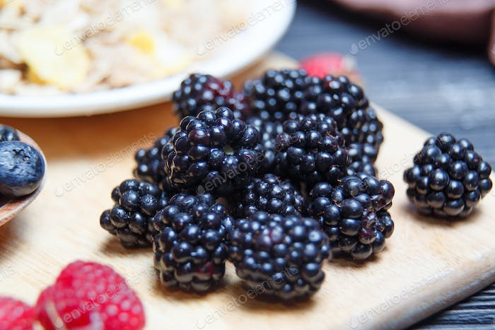 Ripe and sweet blackberries in bowls on wooden table