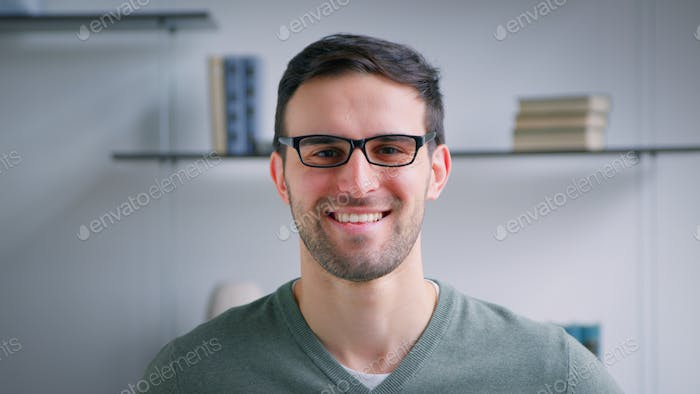 Smiling attractive adult man with glasses looking at camera