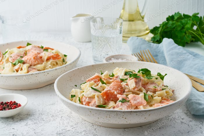Salmon pasta, tagliatelle with fish and creamy sauce. Italian dinner with seafood