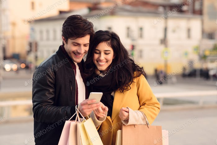 Happy couple using cellphone after shopping in city mall