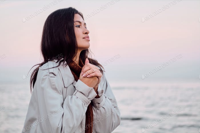 Portrait of attractive Asian girl in trench coat dreamily looking away by the sea