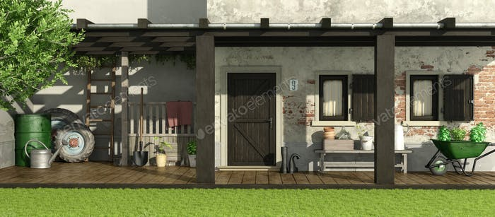 Old house with patio and gardening equipment