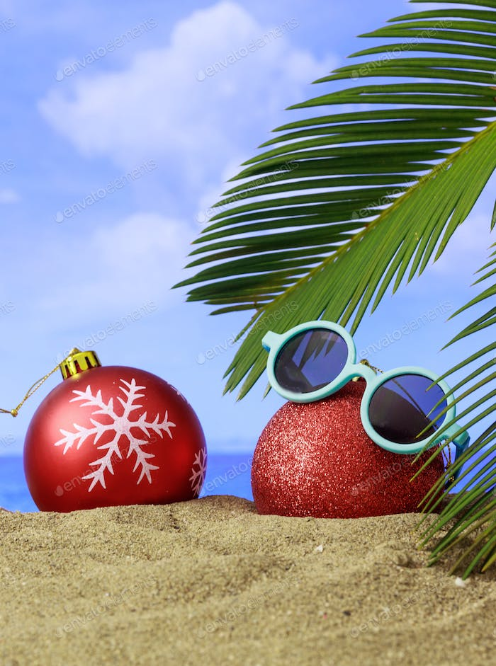 Summer xmas holidays concept. Christmas ornaments on sandy beach with palm tree, blue sea
