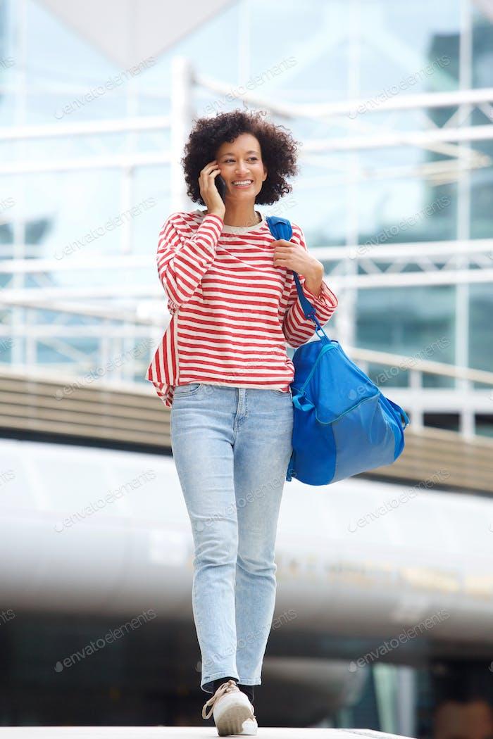 Ganzkörper-Afroamerikanerin zu Fuß in der Stadt mit Handy und Tasche