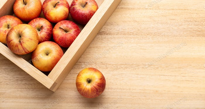 Fuji Apples in crate on wooden table. Copy space