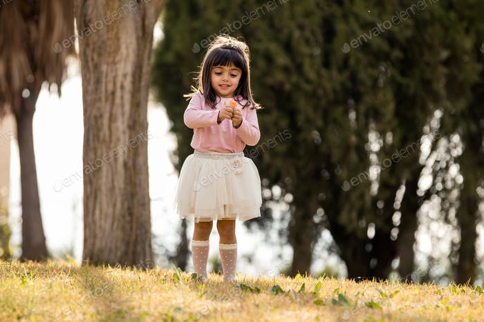 little girl eating sweets in a park