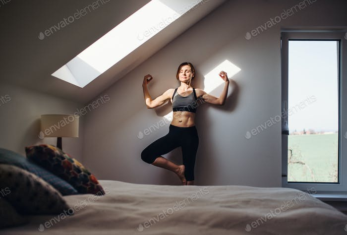 Young woman doing yoga exercise indoors in a bedroom. Copy space.