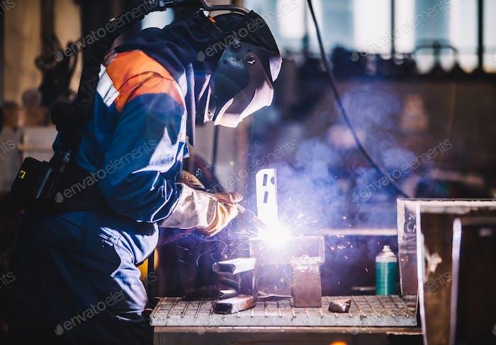 Worker welding in oxygen mask in a factory