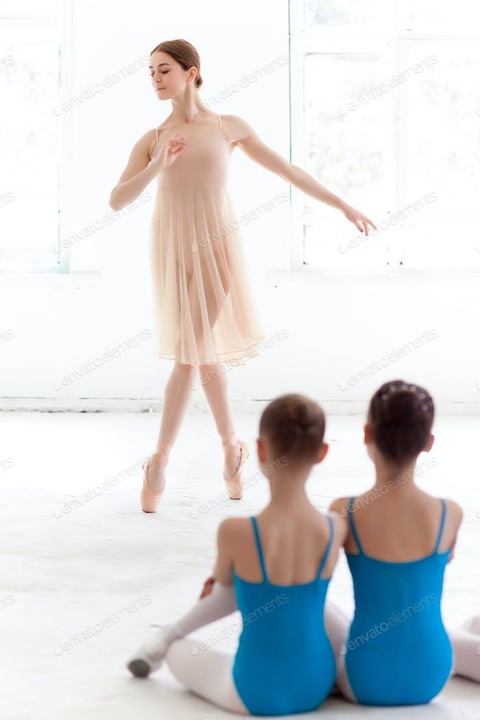 Zwei kleine Ballerinas tanzen mit persönlichem Ballettlehrer im Tanzstudio