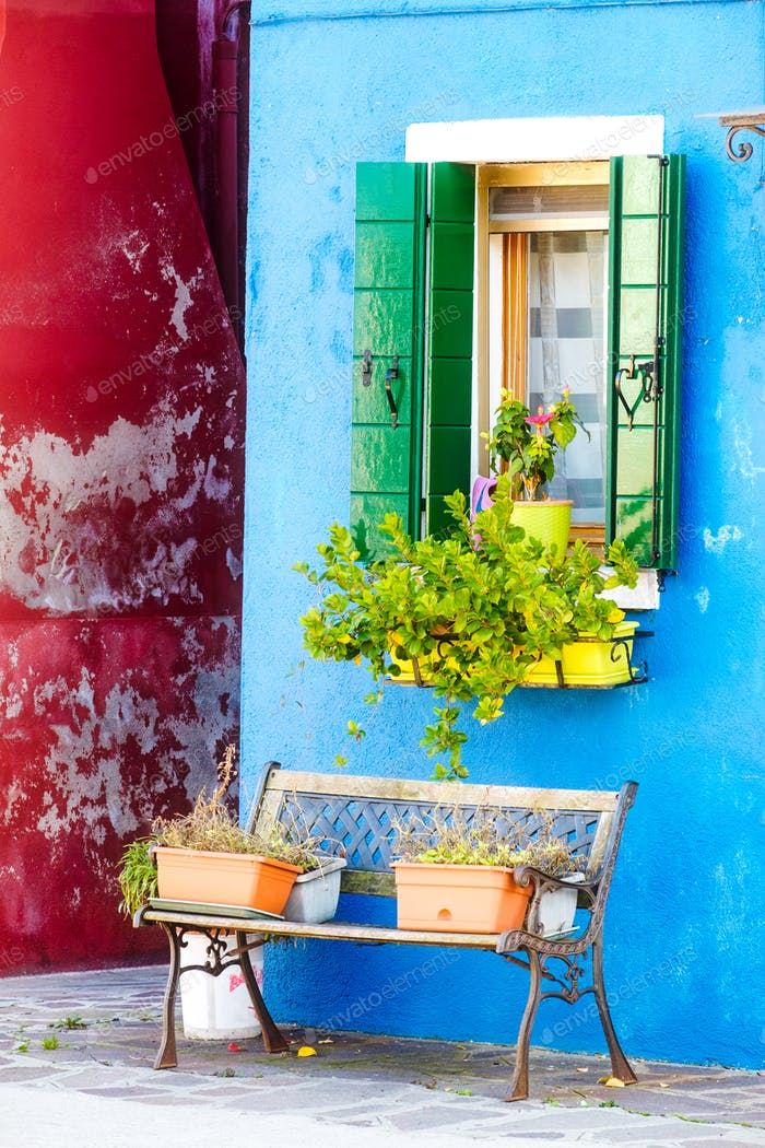 Colorful houses, window with flowers and bench on Burano, Venice