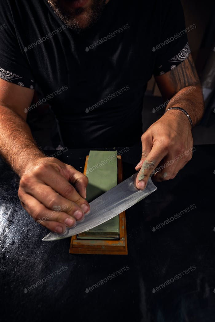 Hands sharpening Japanese chef knife