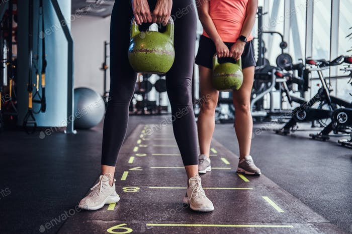 Two sportive girls trains with kettlebells in the modern gym.