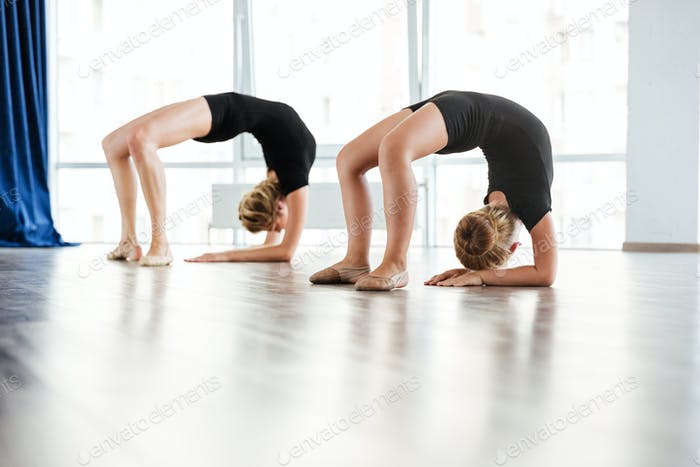 Little girl ballerina and teacher exercising in dance studio