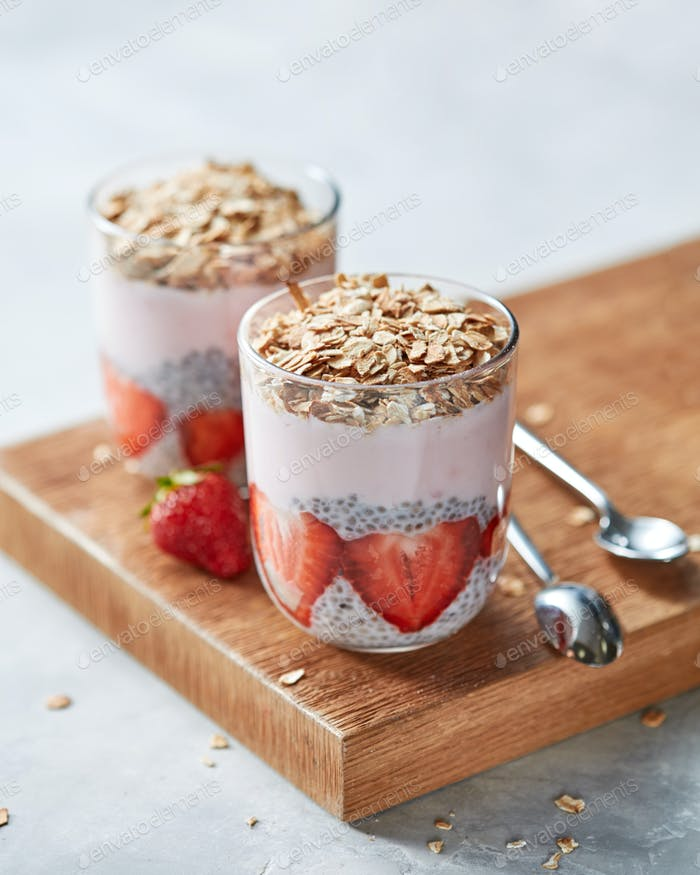 Homemade oat granola with strawberries and in glasses with slices of strawberries, chia seeds on
