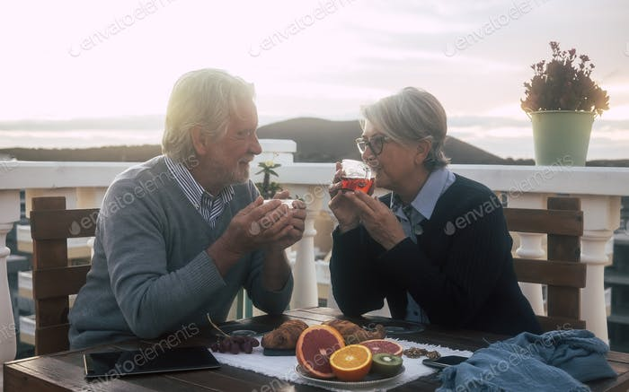 Zwei echte Senioren, Mann und Frau, genießen das Frühstück auf der Terrasse