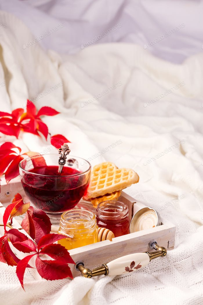 Morning breakfast with red tea, honey and waffles on a bed, homemade food in autumn