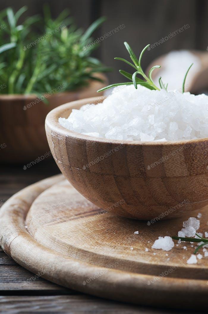 Weißes Salz und grüner Rosmarin auf dem Holztisch
