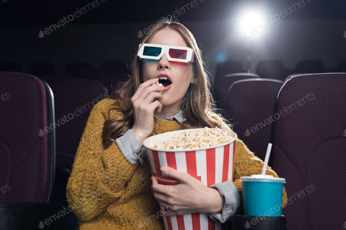 excited woman in 3d glasses eating popcorn and watching movie in cinema
