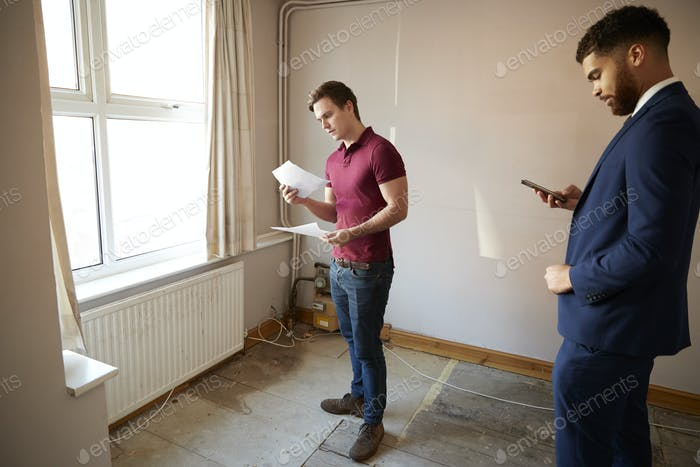 Male First Time Buyer Looking Around House For Renovation With Realtor