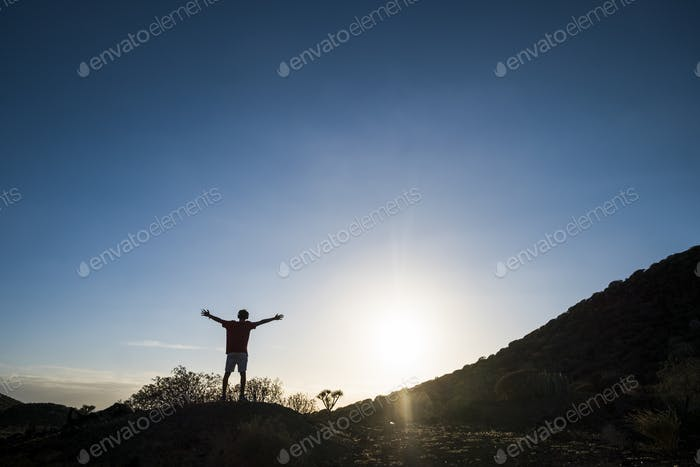 freedom concept lifestyle - man with arms open at the mountains with sunset - positive vibes