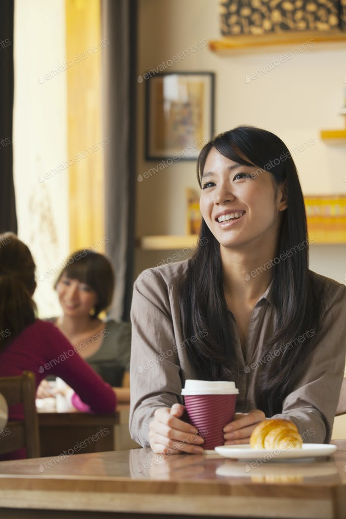 Schöne junge Frau hält Kaffeetasse in einem Café, Peking