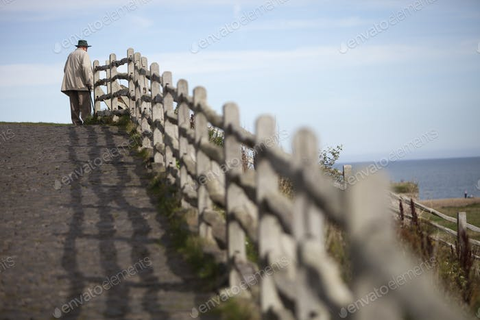 An elderly man standing on the seafront walkway looking out to sea.