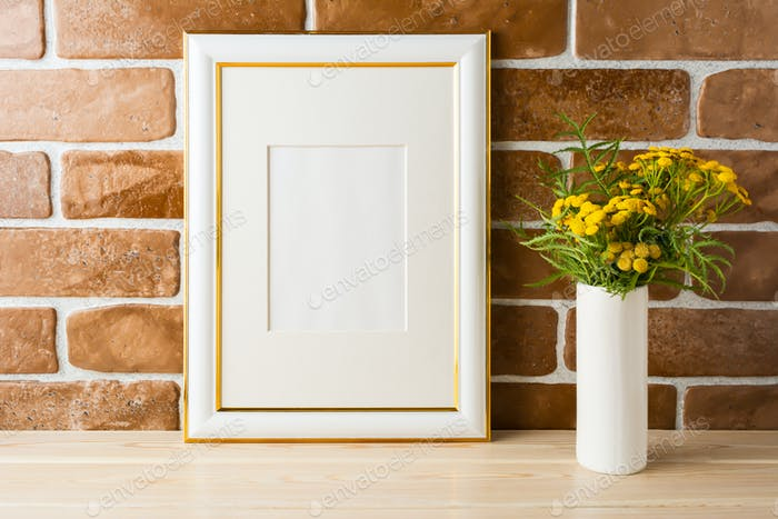Gold decorated frame mockup  yellow flowers near exposed brick w