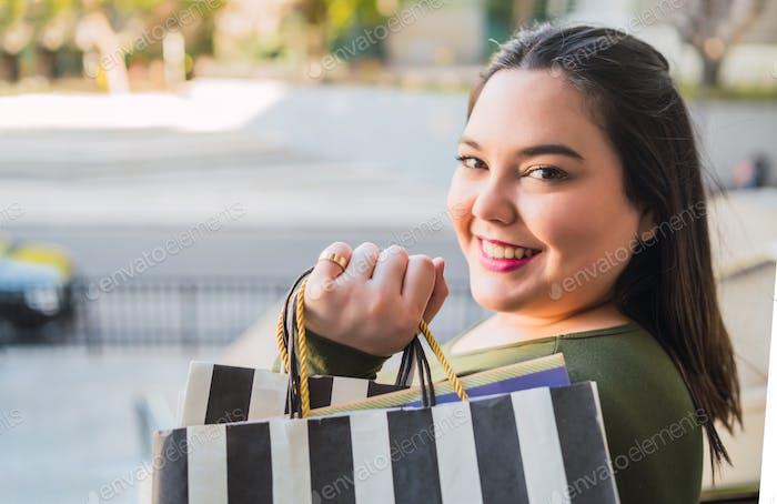 Junge Frau hält Einkaufstüten im Einkaufszentrum.
