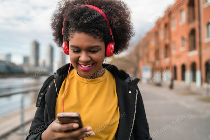 Woman with mobile phone and headphones