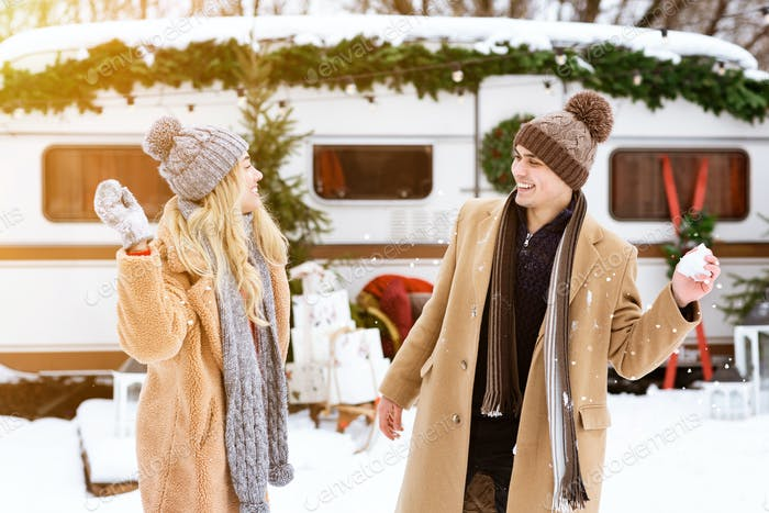 Cheerful Couple Having Fun At Winter Camping, Throwing Snowballs At Each Other