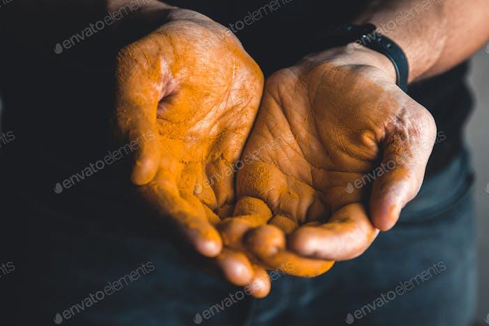 Kurkuma in der Hand Mit schwarzem Hintergrund. Medizin. Nahrungsergänzungsmittel