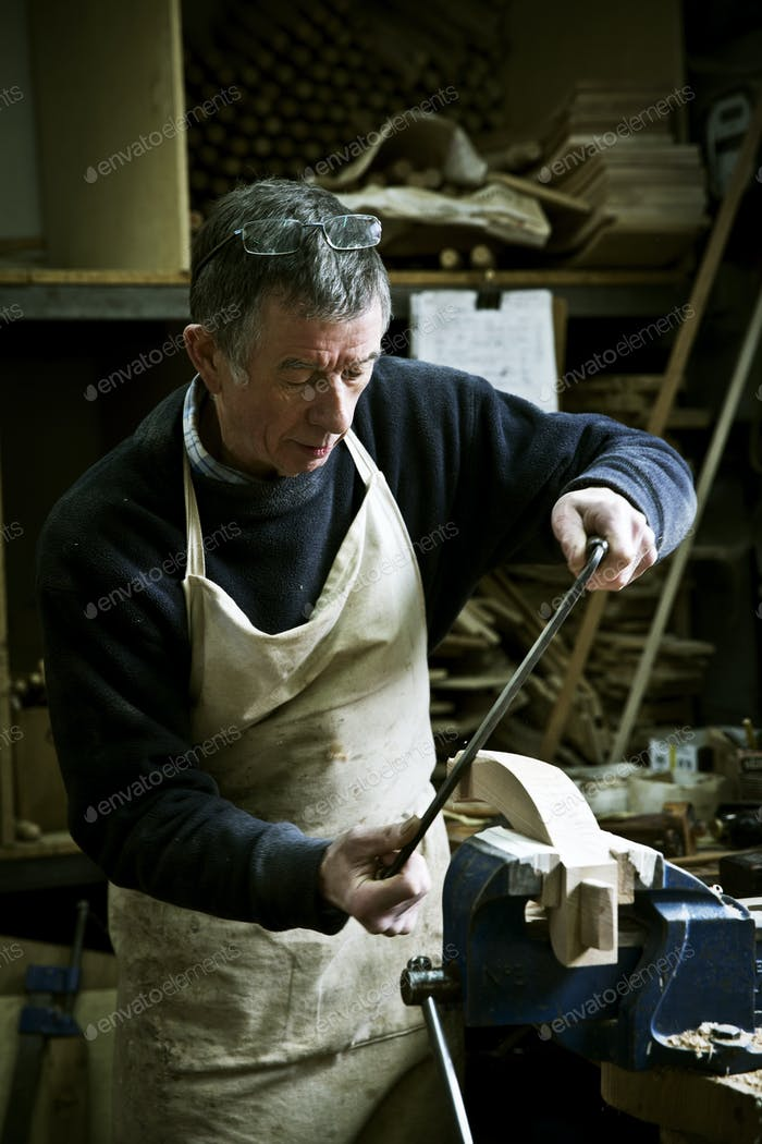 Ein Mann, der in einer Möbelmacherwerkstatt mit einer Raspel auf einer Holzform in einer Klemme arbeitet.