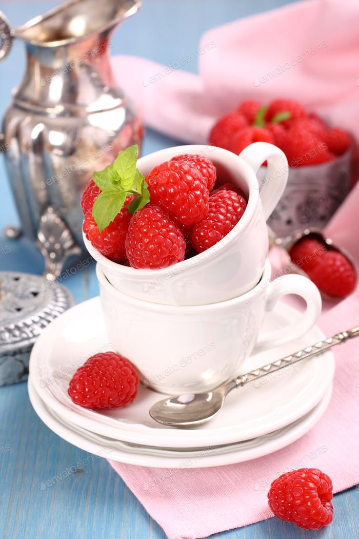 Ripe fresh raspberry with mint in white cup on blue background