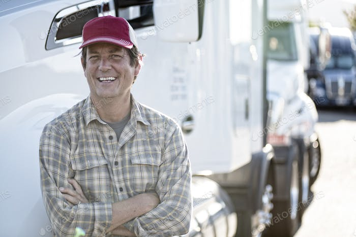Caucasian man truck driver with his truck parked in a lot at a truck stop.