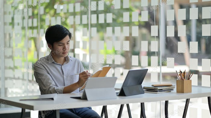 Asian male student with a laptop and stationary preparing to complete thesis to finish university.