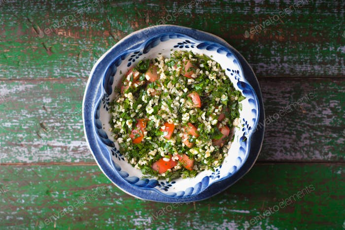 Tabouli salad on the old wooden background top view