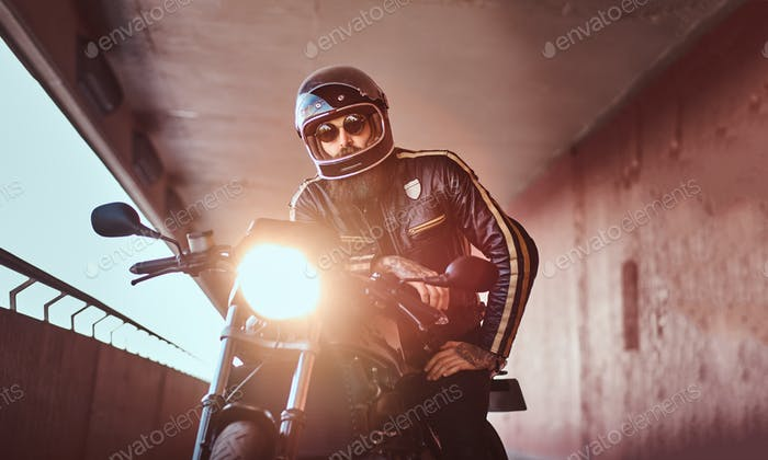 Brutal bearded biker sitting on a retro motorcycle with an included headlight