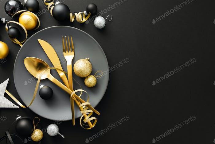 Золотые столовые приборы, подаваемые на тарелку на рождественский ужин