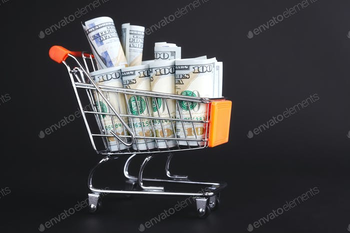 Shopping cart filled with one hundred dollar bills.