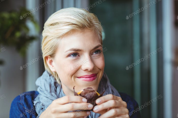 Smiling blonde enjoying a muffin cake at the cafe