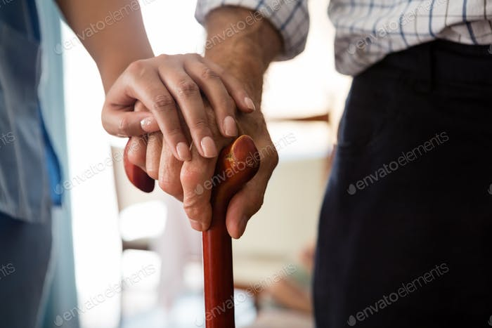 Cropped hands of female doctor and senior man holding walking cane